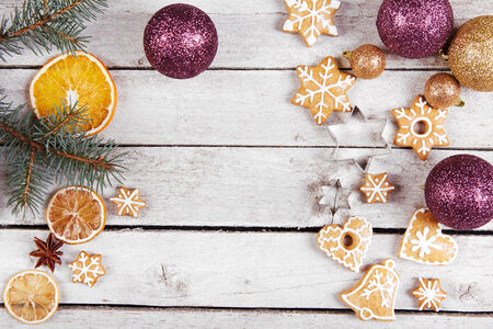 Christmas balls, gingerbread and dried oranges on the table, top view photo