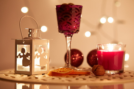 Shining lantern with a candle on the table and Christmas decorations photo