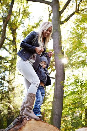 Madre sosteniendo a su hijo para las manos en el bosque
