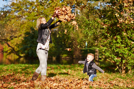 Little boy and mother playing together in the autumn park photo