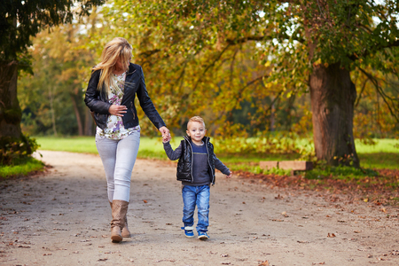 children holding hands: Mother goes along with his son in the autumn park