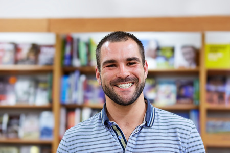 bookshop: Portrait of a man in a polo shirt in a bookstore Stock Photo