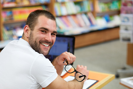 Portrait of a man in a polo shirt with glasses in a bookstore photo