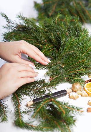 attaches: Woman affixing branches spruce needles on Christmas wreath