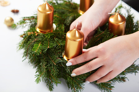 attaches: Woman attaches candle on a Christmas wreath on a white table