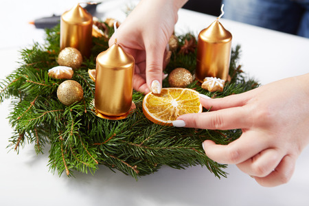 attaches: Woman attaches orange on Christmas wreath on a white table Stock Photo