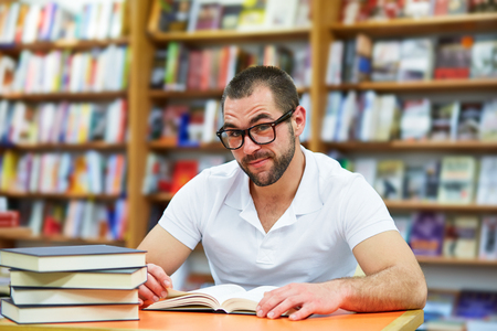 bookshop: Portrait of a man in a polo shirt with glasses in a bookstore