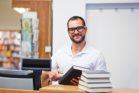 Young salesman at the checkout in a bookstore photo