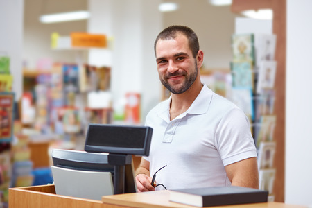 retailer: Young salesman at the checkout in a bookstore Stock Photo