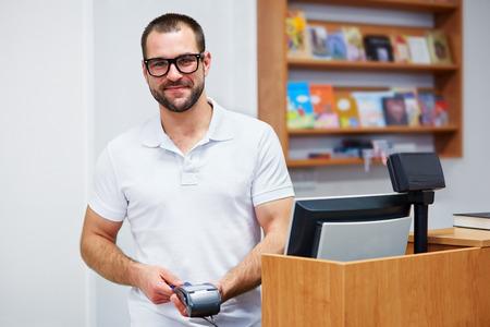 efectivo: Vendedor joven en la caja en una librer�a
