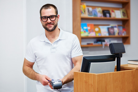 paying: Young salesman at the checkout in a bookstore Stock Photo