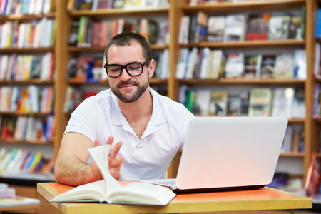Young man working and reading in a library Imagens