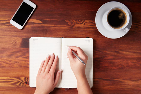 Woman hand writing in a diary, top view photo