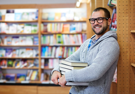 education choice: Young man hold books in the library