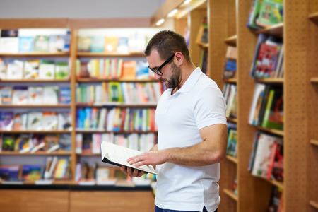 adult education: Young man reading book in the library