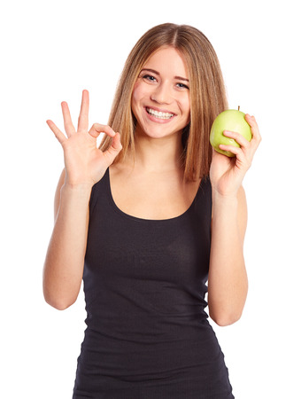 black t shirt: Girl with green apple showing ok gesture on white background