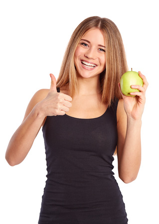Girl with green apple showing ok gesture on white background photo