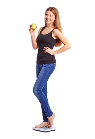Girl standing on weight scale with apple photo