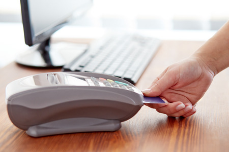 hand card: Female hand controls payment terminal on table Stock Photo