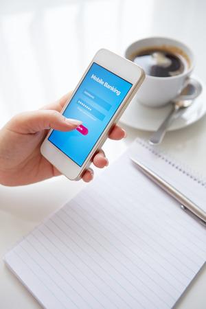Manos femeninas usando la banca m�vil en blanco del smartphone Foto de archivo