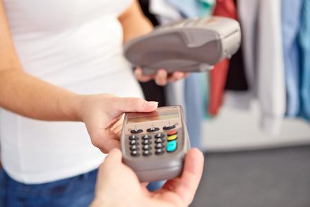 tarjeta visa: Mujer da a los hombres una terminal de pago en la tienda Foto de archivo