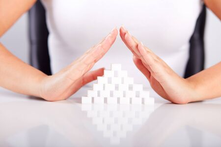 Female hands over a pyramid of sugar cubes photo