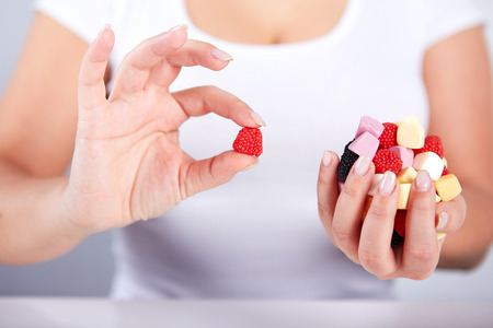 gummy: Woman holding a candies in his hand and the other hand is doing ok gesture Stock Photo