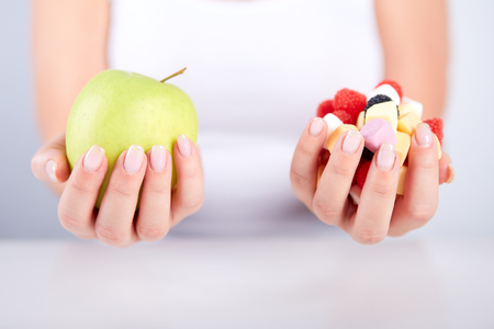 unhealthy diet: Woman holding apple in her hand and in the other hand candies