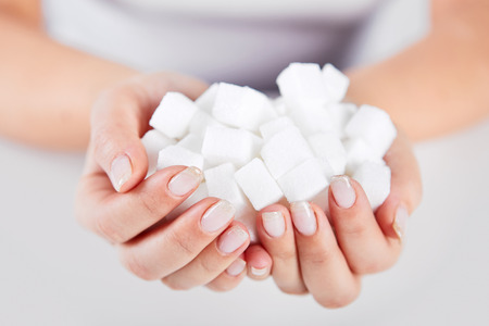 granular: Woman holds in hands of sugar cubes