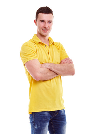 camiseta: Hombre feliz joven en un polo amarillo con los brazos cruzados Foto de archivo