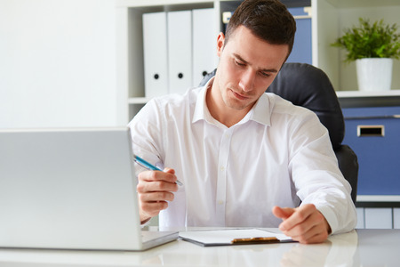 to review: Young businessman signs a document at the office Stock Photo