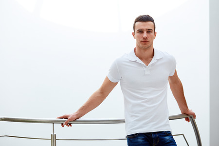 Young man in a polo shirt stands leaning on railing Imagens