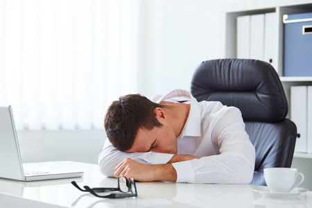 Homem de neg�cios novo na camisa branca que dorme na mesa no escrit�rio
