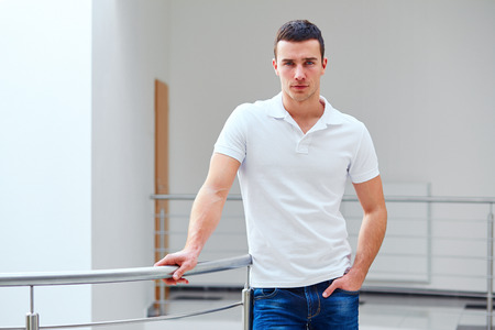 Young man in a polo shirt stands leaning on railing Banque d'images