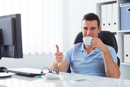 tomando café: Hombre joven de tomar café en la oficina y haciendo un gesto bien