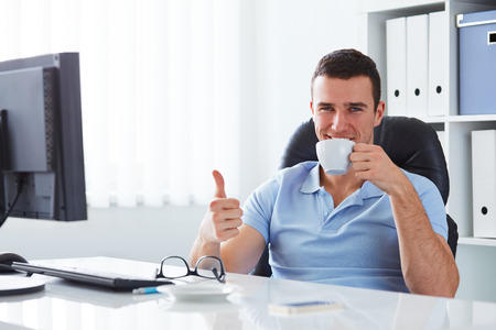Young man drinking coffee in the office and doing ok gesture