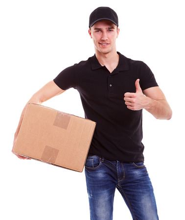 black  cap: Smiling delivery man holding a cardboard box and makes a gesture ok