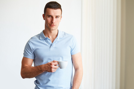 man looking out: Handsome man drinking coffee in the office Stock Photo