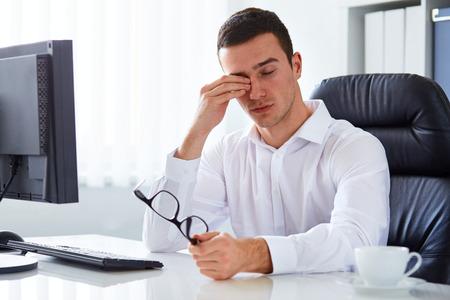 ojos tristes: Hombre de negocios cansado joven frotándose los ojos en la oficina Foto de archivo