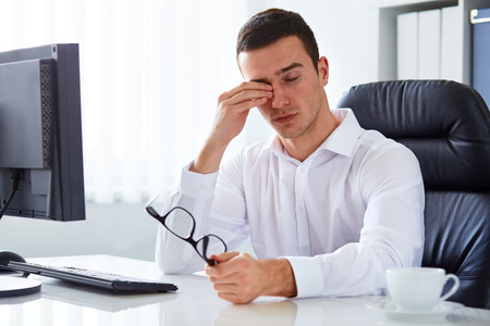 exhausted: Young tired businessman rubbing his eye in the office
