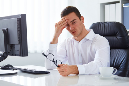 exhausted worker: Young businessman under stress with headache and migraine Stock Photo