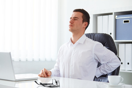 dolor de espalda: Joven empresario ha Dolor de espalda en el trabajo con un ordenador portátil Foto de archivo