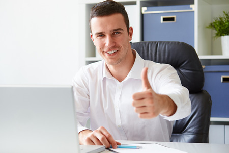 thumbs: Businessman working on laptop and making the ok gesture