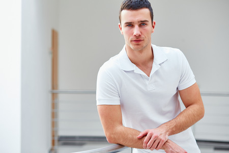 Young man in a polo shirt stands leaning on railing Stock Photo