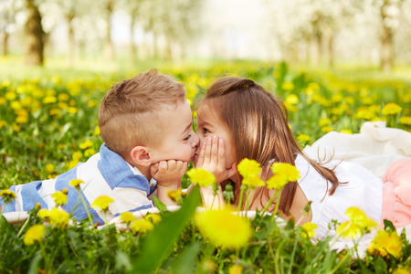 Girl kissing a boy in a blossoming orchard