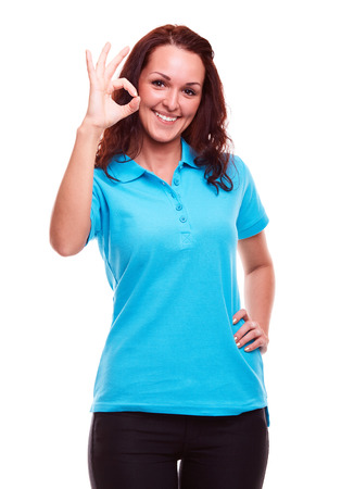 Smiling young woman gesturing ok, on a white background