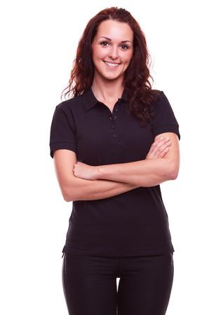 Mujer sonriente en la camisa de polo negro con los brazos cruzados, en un fondo blanco