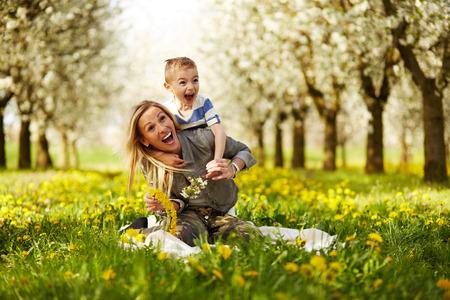 madre e hijo: Madre jugando con su hijo en un huerto en flor
