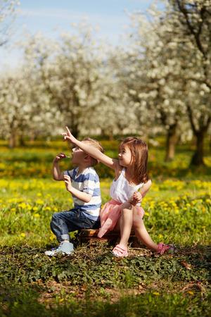 niños sentados: Chica sentada con el niño en un huerto en flor