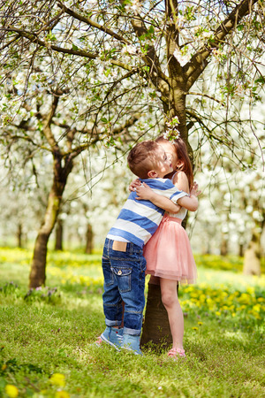 brother: The boy hugged girl in a blossoming orchard,
